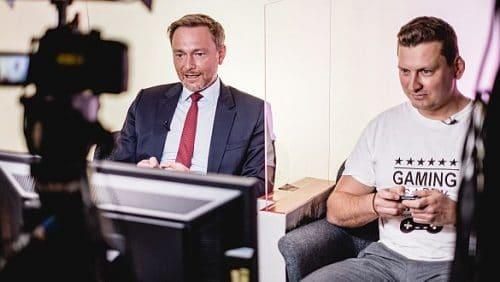 """Wenn Zocken auch Chefsache ist: Der FDP-Vorsitzende Christian Lindner schaut bei seinem Fraktionskollegen Mario Brandenburg vorbei, der regelmäßig streamt, wie er Videospiele  streamt. Hier besiegt Brandenburg seinen Chef bei """"Mario Kart"""". (c) FDP"""